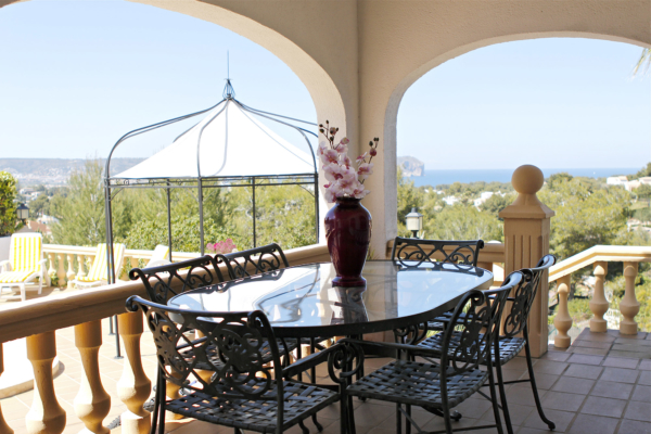 Balcony with glass table in modern villas in spain has stunning views of the sea and Montgo.